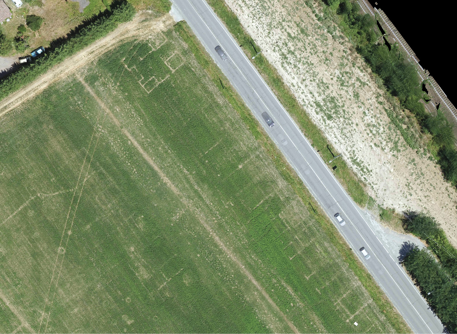 below A drone image showing cropmarks that reveal the ancient Via Postumia (a little to the left of the modern road) and traces of adjacent buildings.
