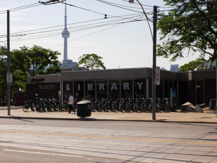 A photo of one of Toronto's library branches, with the CN tower in the background.