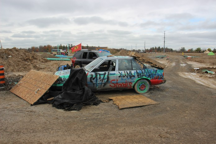"A grey car covered in spraypaint, and the message ""land back"""