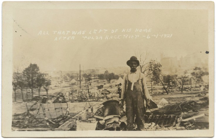 Man stands facing camera in front of ruins of home