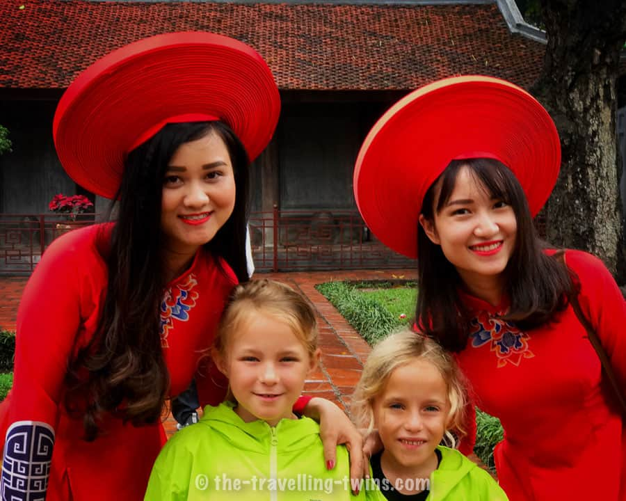 our girls with two vietnamese women dressed in traditional Ao Dai- long fitted dress. they were as well wearing wooden clogs - guoc moc vietnam souvenirs