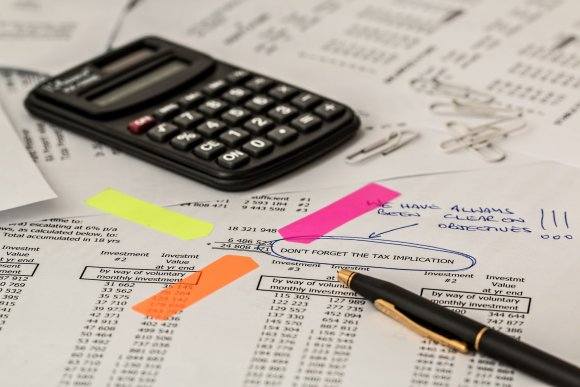 A picture of a calculator and lots of papers. The article is about paying tax on UK side hustles.