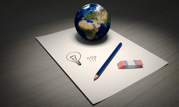 pencil, eraser and a globe on a piece of paper.