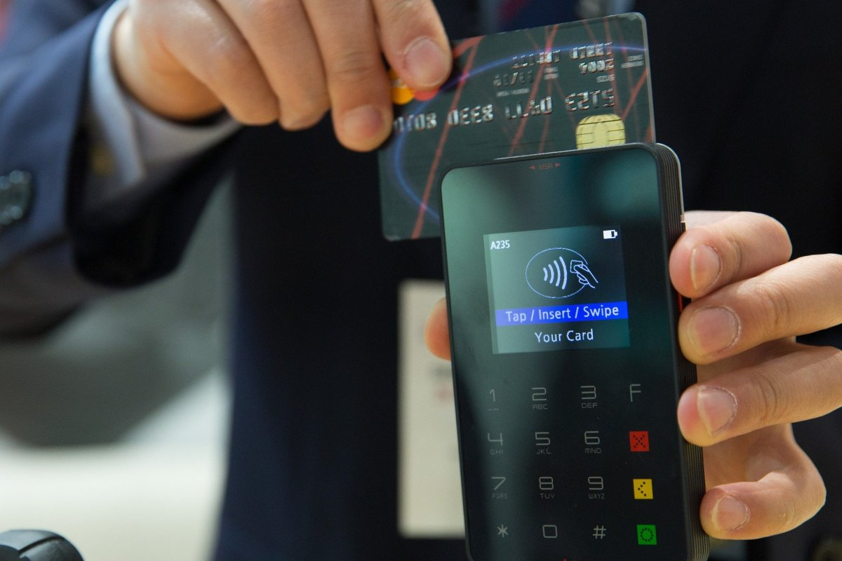 Man holding credit card to card reader to demonstrate the contactless limit increase
