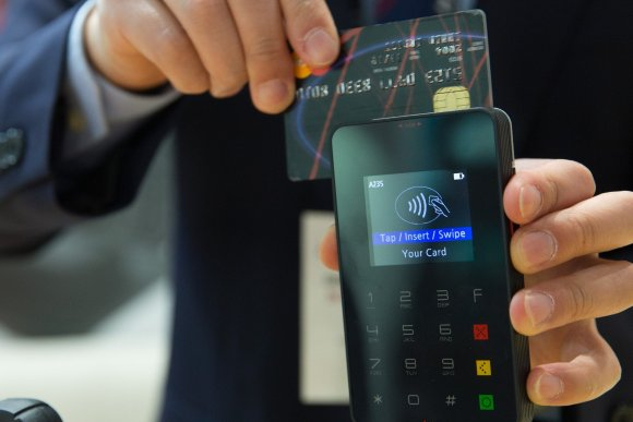 Man holding credit card to card reader to demonstrate the contactless limit increase limit i
