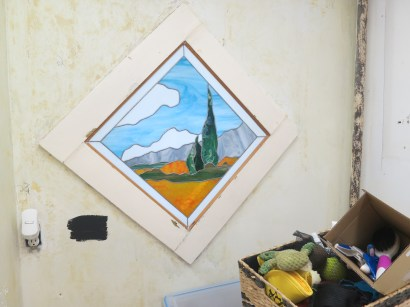 Stained glass with a black paint sample on the wall.