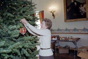 First Lady Nancy Reagan decorating the White House Christmas Tree in The Blue Room in 1981