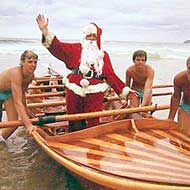 Santa arriving at the beach by boat