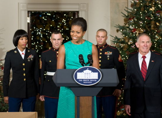 The first lady speaks in the Grand Foyer of the White House alongside members of the US Marine Corps and Toys for Tots President Retired Lieutenant General H.P. Pete Osman (R) as she thanks volunteers who decorated the White House for the Christmas holidays
