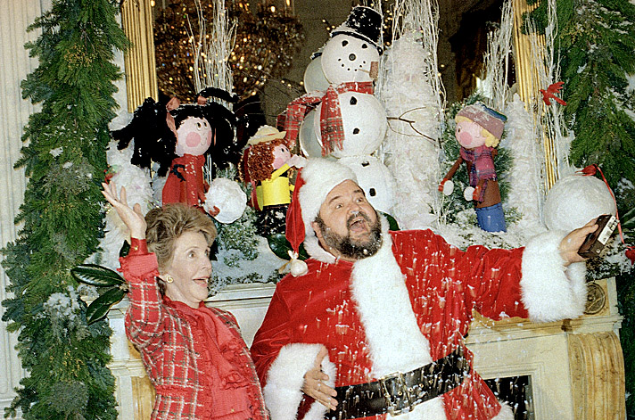 First Lady Nancy Reagan and Santa aka Dom DeLuise, throw some artificial snow in the air during a press preview of White House decorations in 1987