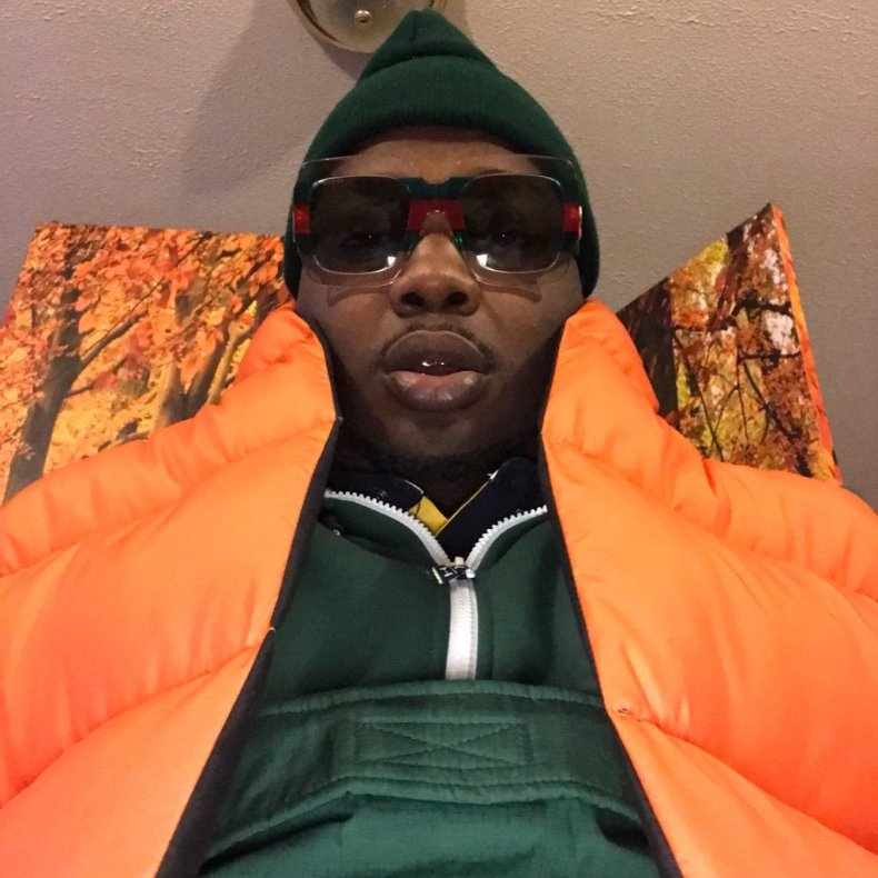 Soulebrity in an orange jacket wearing shades