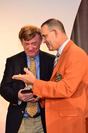 Dick Weiss, FWAA Past President and 2013 Bert McGrane winner, accepts the Edwin Pope Vanguard Award, which is presented to a media person who has been important in the coverage of the Orange Bowl over the years. Discover Orange Bowl Executive Director Eric Poms makes the presentation at a luncheon during bowl week. (Photo courtesy of the Discover Orange Bowl)