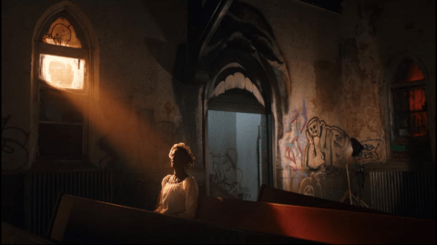 A woman sits in a hidden decrepit chapel dedicated to Candyman