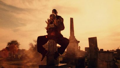 The end of the opening sequence of a corpse holding a severed head upon a tombstone