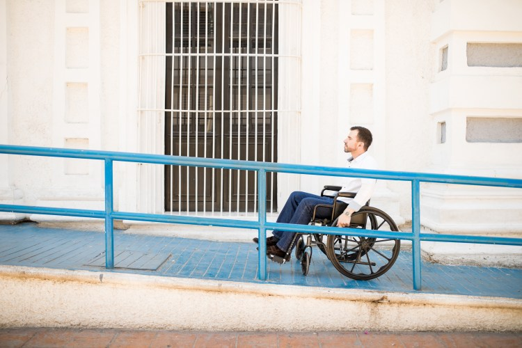 Profile view of wheelchair user moving up wheelchair ramp