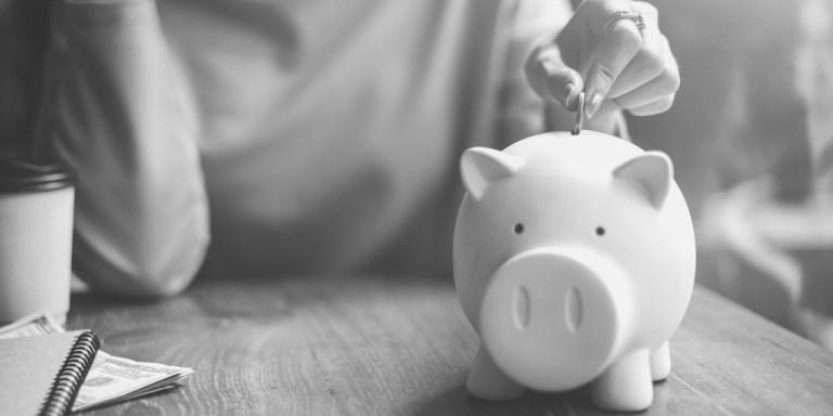 Woman putting coin into a piggy bank