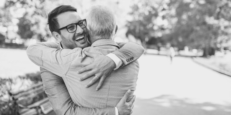 Man with glasses hugs older man in a park