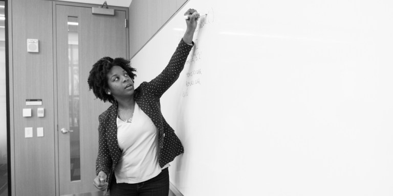 Woman writes on whiteboard in classroom