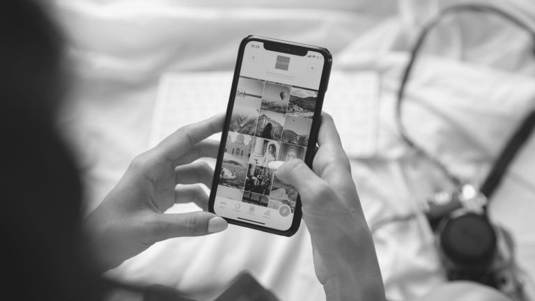 Influencer sitting on bed holds phone with Instagram grid pulled up camera in background