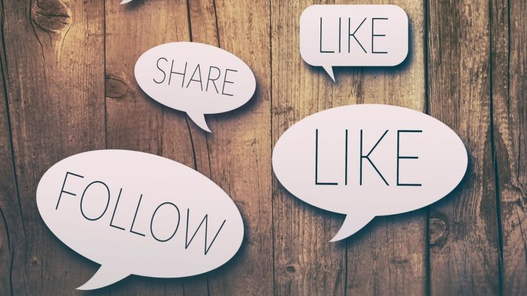 Speech bubbles that say follow, like, and share against a wood board background