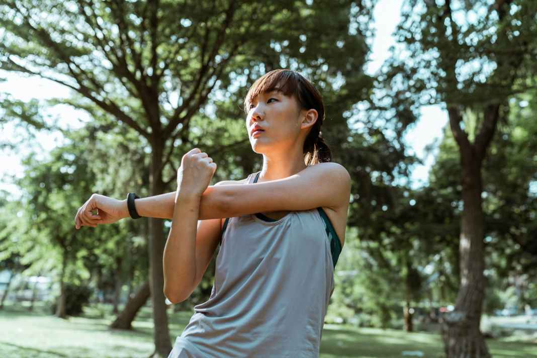 ethnic sportswoman stretching arms during training in nature
