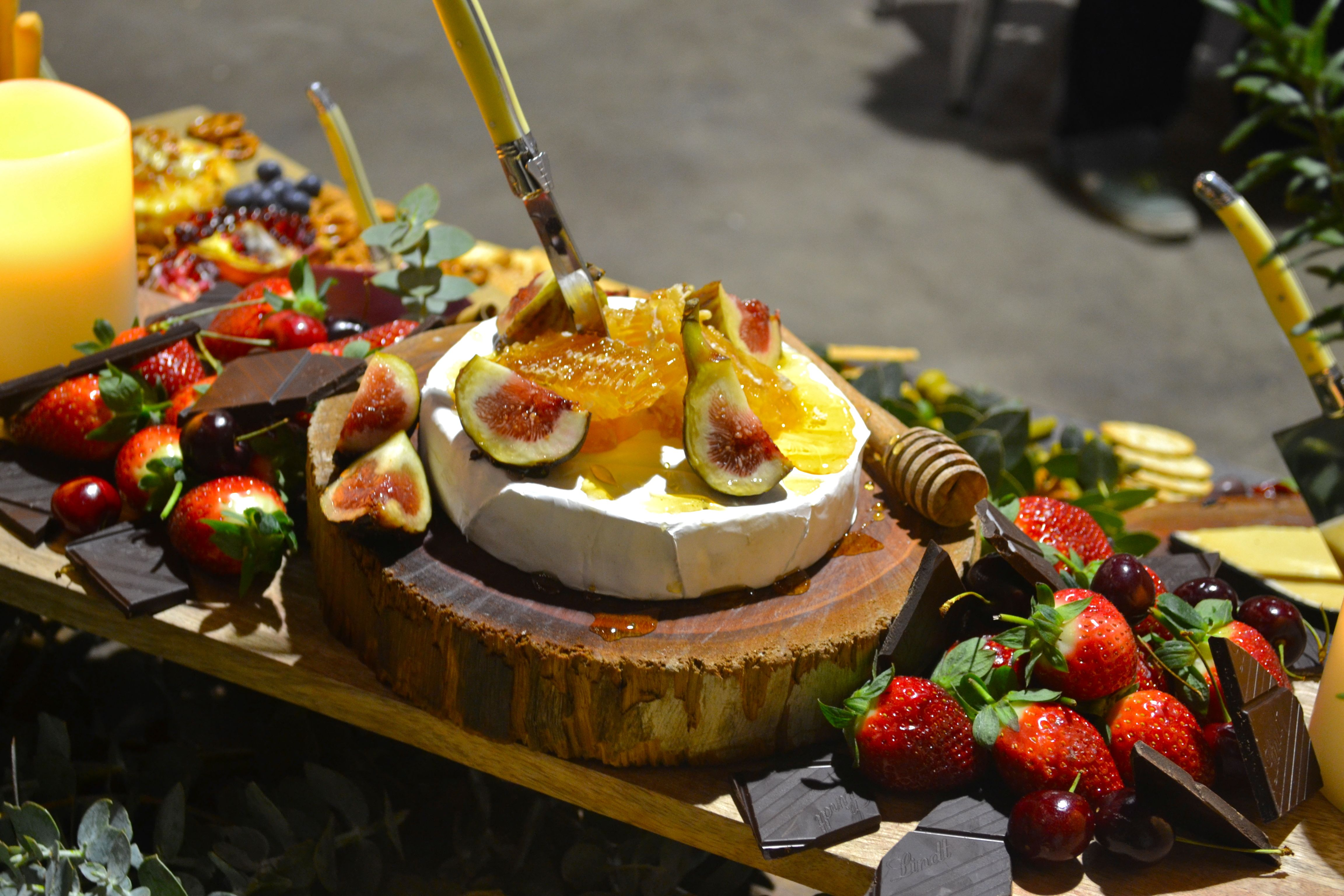 Honey-drizzled brie with fresh figs, surrounded by dark chocolate and strawberries.