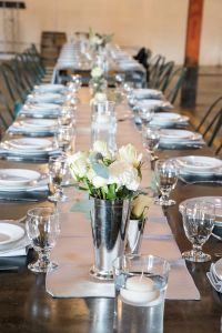 Table with table runner, small flower vases, white flowers