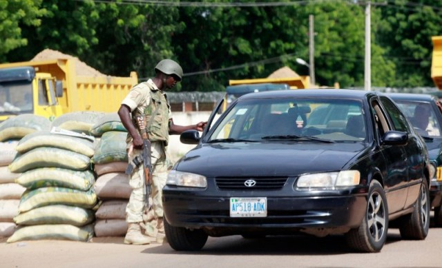 On the road: A soldier searches a car at a Maiduguri checkpoint, one of dozens guarding routes into the city