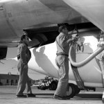 """Technicians servicing the Bell Aircraft Corporation X-1 in preparation for a flight. The X-1 is mated with the Boeing B-29. The hooks and strap that holds the X-1 in place under the B-29 can be seen just above the hand of the technician with the hose. The strap continues under the belly of the X-1 and holds the aircraft to the mothership until the word comes to """"launch"""", and then the shackles are released. (NASA photo)"""
