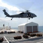 An MH-60S Sea Hawk helicopter carries one of the 333 loads of cargo from the Military Sealift Command hospital ship USNS Comfort (T-AH 20) as the ship is anchored offshore near Port-Au-Prince (US Navy photo)