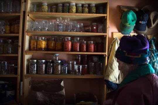 Jane Faller dons a coat in her mudroom containing canned goods on Wednesday. Everywhere she looks, she sees reminders of her late husband. Jane and Bob canned the goods last summer and they remain stored on a shelf he built for them next to a collection of his favorite hats.