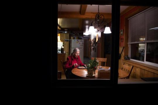 "Jane Faller eats dinner by herself as snow settles outside her home in Republic, Wash., on Tuesday. Her children worry about her making it through the winter, but her friends Steve and Deb Anthes regularly check in on her, and a neighbor plows her driveway. Still, the solitude can be unrelenting. ""It's an empty home,"" she said."