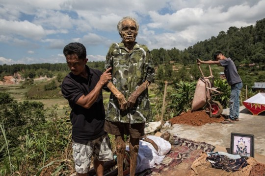 A man holds the corpse of Tang Diasik, who died six years ago, as he dries the corpse during the Ma'Nene ritual in Ba'Tan village, Toraja, South Sulawesi, Indonesia.