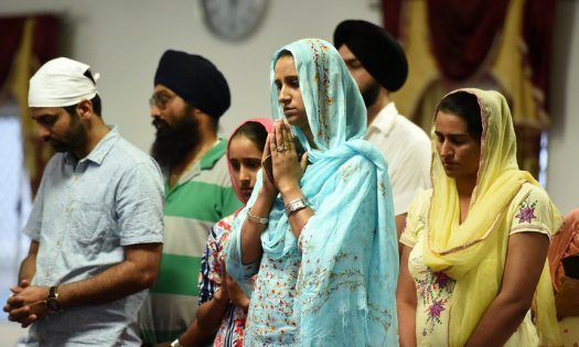 Mourners attend a vigil for bus driver Manmeet Alisher at a Sikh temple in Brisbane, after he was burned alive when an incendiary device was allegedly thrown at him while he was letting passengers on at Moorooka