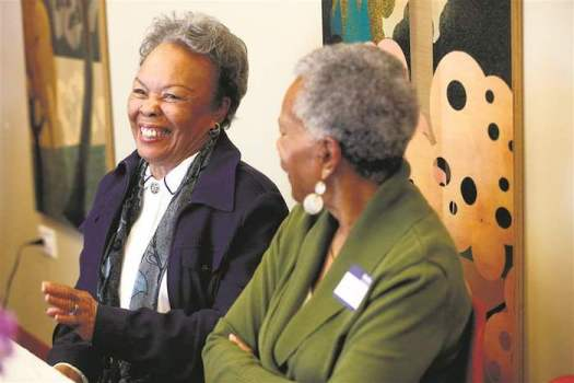 Alice Bishop, left, of Toledo, shares a story while laughing during a support group for widows.