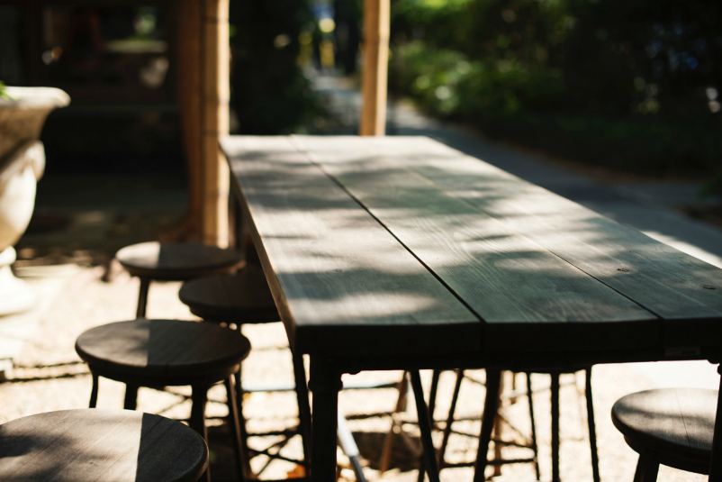 Unsplash image empty wooden table and chairs outside.