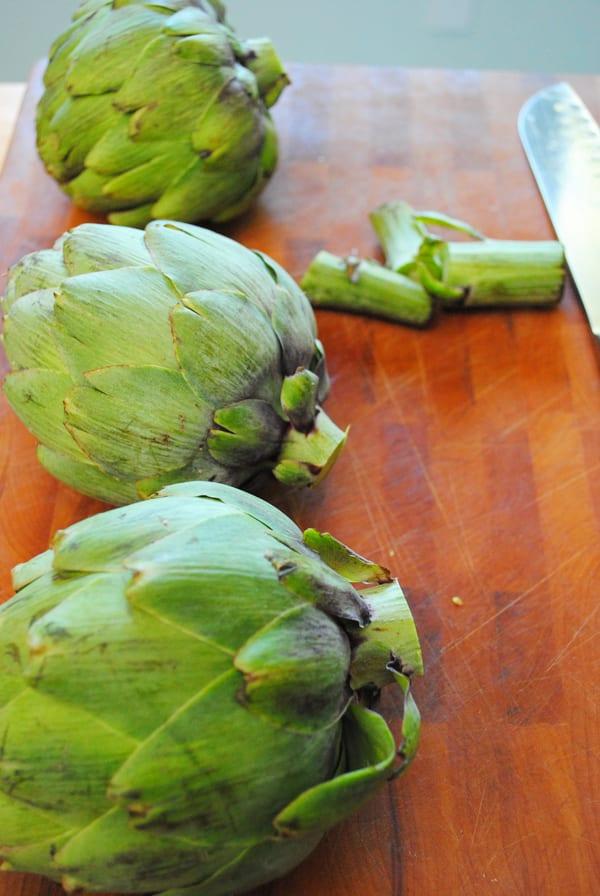 Trim the stems off the artichokes