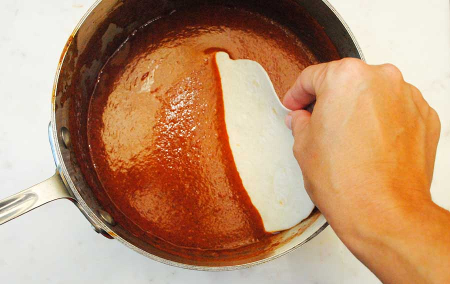 Soaking the tortillas in sauce for Rotisserie Chicken Enchiladas