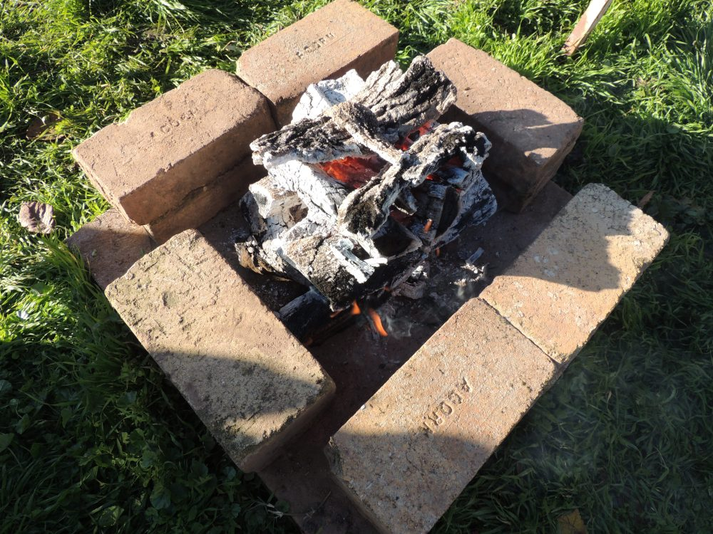 A fire surrounded by fire bricks for a Tuscan grill