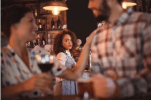 Young woman watches a couple having wine and chatting enviously. Looks like we have our nice gal character