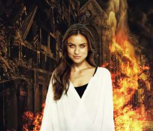 woman with flaming eyes in front of a burning building