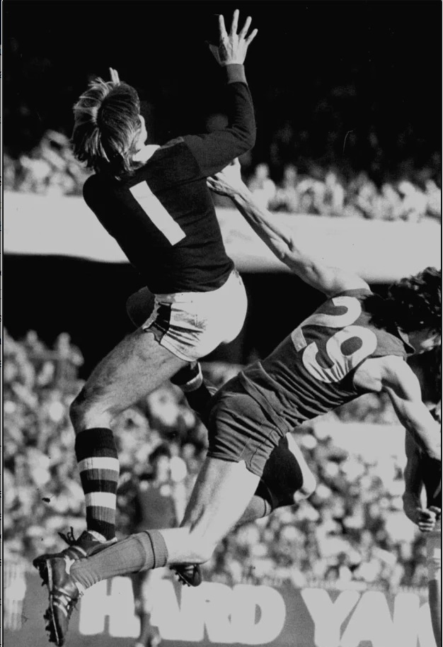 Trevor Barker flies high over Andrew Coir of Melbourne in Round 12 1980 at the MCG.