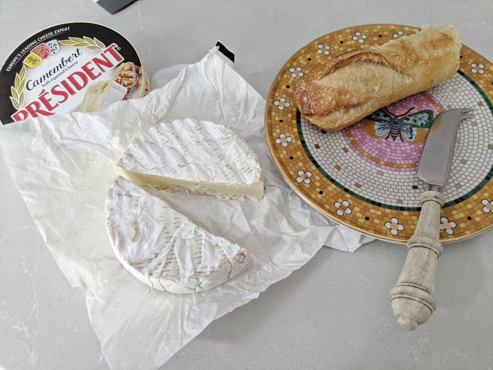 a wheel of cheese along with a plate, baguette, and cheese knife