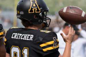 Punter/place kicker Bentlee Critcher spins a ball on his fingertip on the sideline. Photo By: Monique Rivera, Photographer