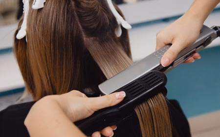 girls using hair straightener