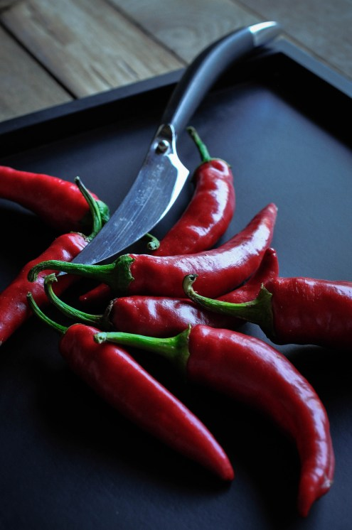 Chillies and knife on black tray