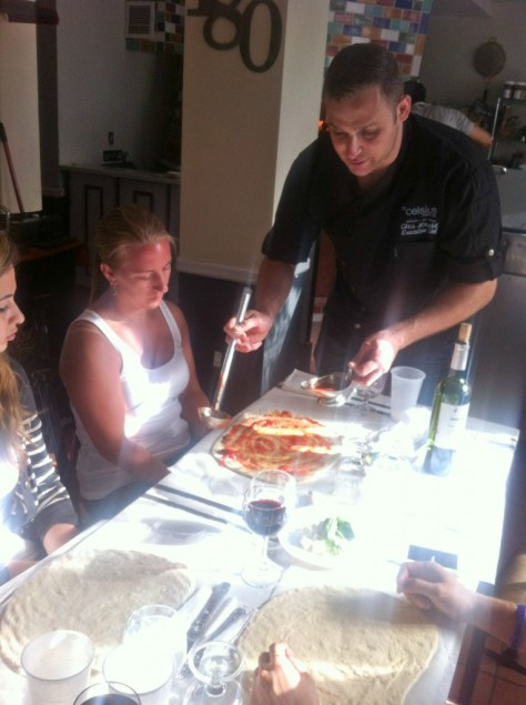 Chef Chris demonstrating how to sauce the pizza