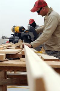 Airman 1st Class Bruce Ramsey from the 557th Expeditionary RED HORSE Squadron uses a chop saw to cut a 2/4 structure on Joint Base Balad, Iraq, Jan. 13, 2010. RED HORSE squadrons construct some of the structures needed by contingency and special operations worldwide. (U.S. Air Force photo/Senior Airman Brittany Y. Bateman/Released)