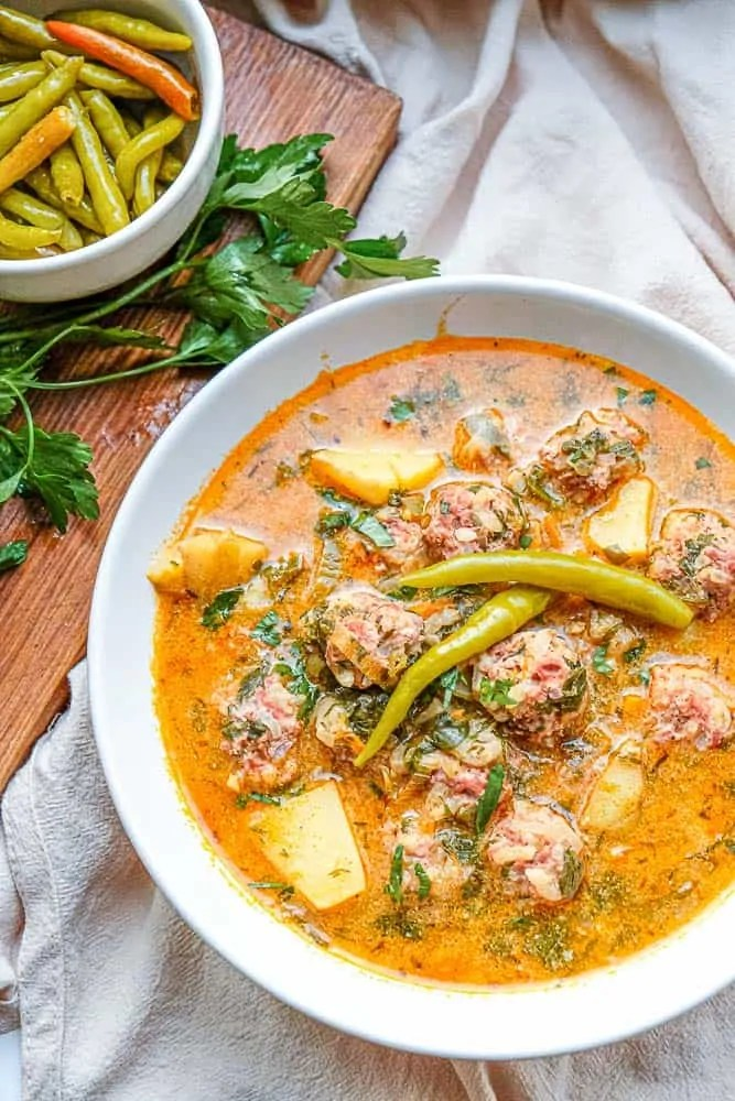 This classic Romanian soup features hearty porcupine meatballs swimming in a creamy and flavourful broth dotted with diced veggies and fresh herbs like lovage, parsley and dill. Serve with hot pickled peppers and crusty bread for a perfect cold weather meal.