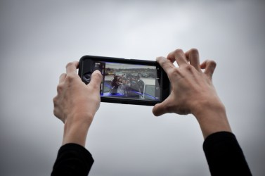 Lifting Up the Camer. Two hands were holding a smarphone (photo by Iksander)